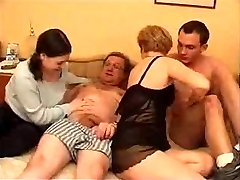 Mature couple with youthful couple in bed