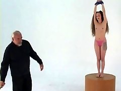Longhaired bondage brunette with small baps stands on pedestal for whipping