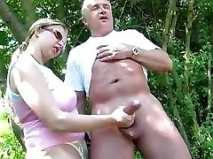 Mature duo outdoors and she gives him a hand job of the schlong