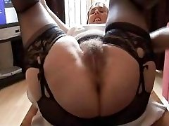 Hairy huge-titted mature woman in slide and girdle does upskirt and striptease show