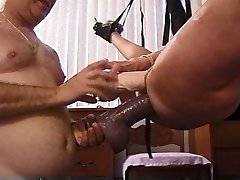 Mature Blond hoe in sling stuffed with huge dildos