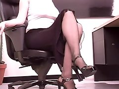 Busty brunette secretary plays with a large fake penis at her desk