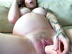 Pregnant brunette slutty masturbates with huge faux-cock