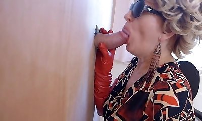 Cougar in boots watches porn and enjoys gloryhole oral job