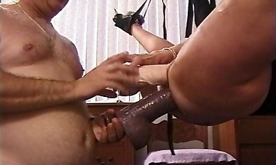 Mature Blonde super-bitch in sling stuffed with huge dildos