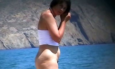 Hot mature beach nudist unwraps of her clothes and gets wet
