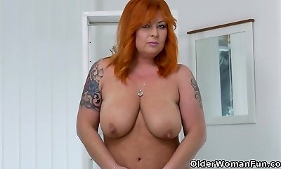 Red-haired milf Alex strips off and fingers her mature beaver