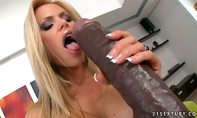 Skanky blond mom gives blowjob to huge dark-skinned dildo