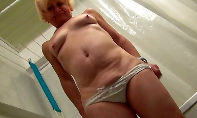 Ugly scaring ash-blonde oldie takes a douche and teases her mature cunt