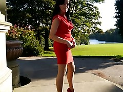 Sexy Tricia takes a stroll outdoors wearing a tight red dress with matching high heel shoes and...
