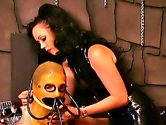 Mistress in latex dress roping a slave girl in bondage preparing her for training