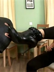 Lustful babe in black boots pushing huge strapon inside tight asshole of her slave