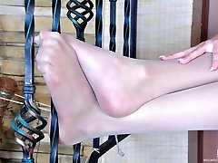 Frisky girl unbuckles her strappy sandals to show her slender nyloned feet