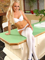 Pretty blonde poses over her kitchen counter, flashing her white cotton panties and hold up...
