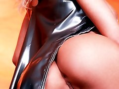 busty European blonde pulls up shiny latex dress
