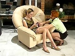 Lustful milf tempting a lez curious girl into hot dildo toying in armchair