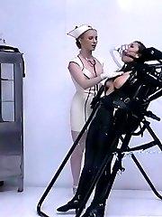 Domina in nurse latex uniform training pretty female slave in black latex suit