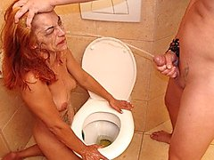 Mature slut gets pissed in the face on a public toilet