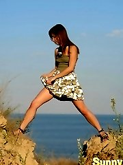 Sexy teen girl on the seaside getting out of her military styled dress