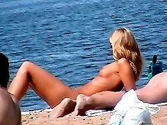 Charming slim blond with small sexy tits was tanning naked on the beach