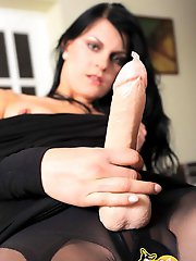 Sultry vixen in black strokes her strap-on and fills a condom