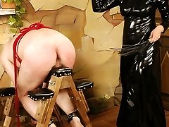 Mistress in black latex dress restrains male slave on a saw-horse for bare-butt punishments