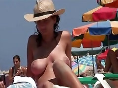 Topless girl with big boobs and a hat on the beach