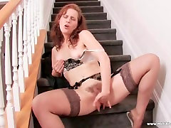 Ginger MILF fucks her all fucked with clothes pussy on the stairs