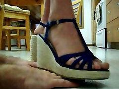 Hand trampling by beautiful feet in blue platform sandals