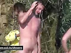 Nudists showering in a waterfall