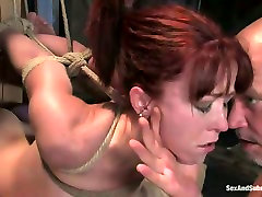 Hanging above the floor tied up redhead has to suck massive strong cock