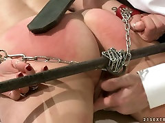 Doctor spanks his patients ass with a leather paddle in rough BDSM way