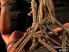 Sassy brunette bitch with big boobs is tied up and hanged down the ceiling