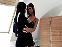 Lesbo cuties embrace and kiss passionately in the living room