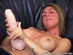 Demoing masturbation while topless and with a huge dildo on hand