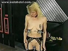 Slave with tiny tits walking around with large metal clamps on her nipples and pussy