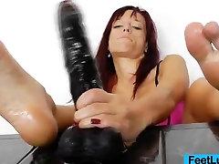 Redhead gives stirring footjobs to dildo