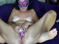 Mature masturbating while wearing mask