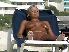 חם MILF בלונדינית עם ציצים גדולים מקבלת השמש-השיזוף בחוף נודיסטים