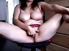 Busty mature woman spreading legs to masturbate her twat