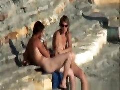 Nudist couple by a rocky seashore