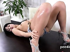 Enchanting sweetie is peeing and masturbating shaven cunt