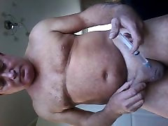 BDSM scrotum filled up with water ,injected with a syringe