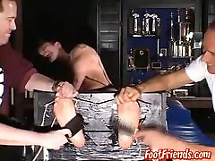 Two older guys having fun tickling a tied up younger dude