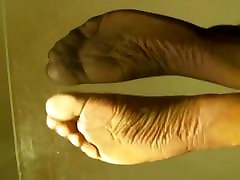 Soles arches view in black nylon socks, pink toes and one na