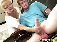 Blonde mature with spex jerking cock