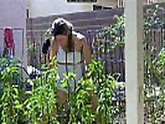 www.voyeurpissing.com - Amateur lady pissing on her plants in a gerden in public