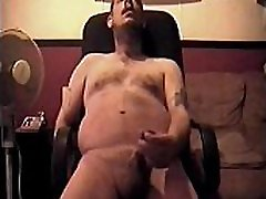 bisexual amateur sits in his computer chair naked masturbaiting to porn and shoots his load