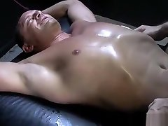 Tattooed muscled hunk tickles bondaged cum for two babes with feathers