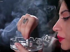 A girl smokes a cigarette and inhales deeply to feel the kick of nicotine.